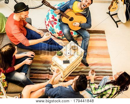 Group of trendy friends having fun in hostel living room - Happy young backpackers enjoying time together playing music with guitar and drinking beer - Focus on wood table - Warm contrast filter
