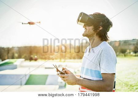 Bearded man using a drone with remote controller wearing virtual reality glasses making photos and videos - Young guy having fun with new vr technology trends - Focus on face headset - Warm filter