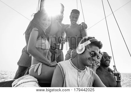 Happy friends making boat party drinking beer and listening music with dj set - Young rich people sailing on summer holidays in miami - Focus on left guys faces - Black and white editing - Warm filter