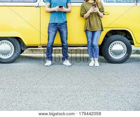 Young friends using mobile cell phones next minivan on urban street - Travel people addiction to new technology trends - Focus on hands smartphones - Warm filter