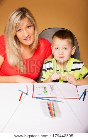 Family children and happy people concept - mother and son drawing together mom helping with homework daycare