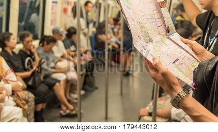 Tourist looks and trying to search location on map inside a MRT subway train runs in Bangkok. Many people in Bangkok used subway to save time.
