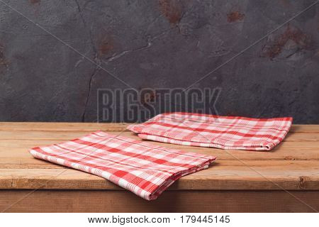 Empty wooden deck table with tablecloth over balck wall background for product montage display