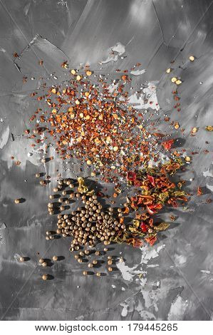 Scattered Different mixture of seasonings in front of gray concrete background