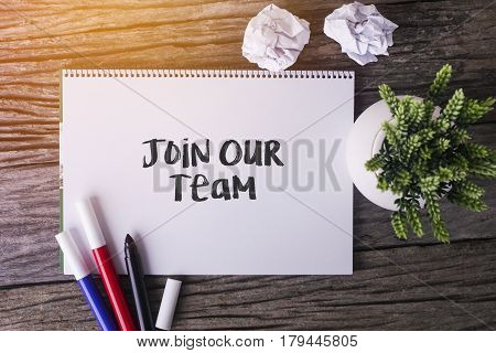 Join Our Team Word With Notepad And Green Plant On Wooden Background.