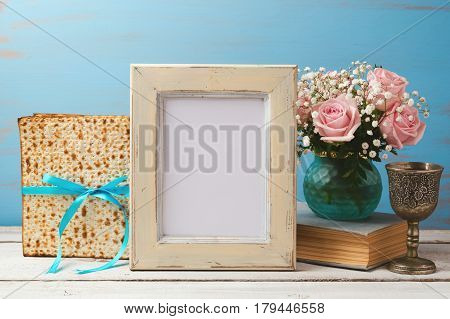 Jewish holiday Passover Pesah concept with poster photo frame matzoh and rose flowers bouquet on wooden table