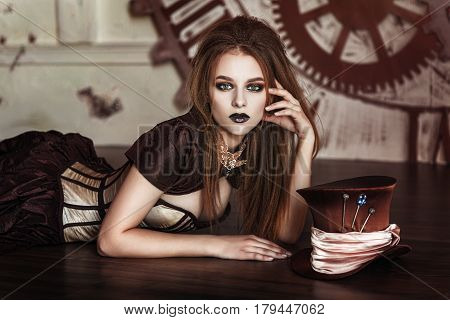 Portrait of a beautiful steampunk woman near big clock