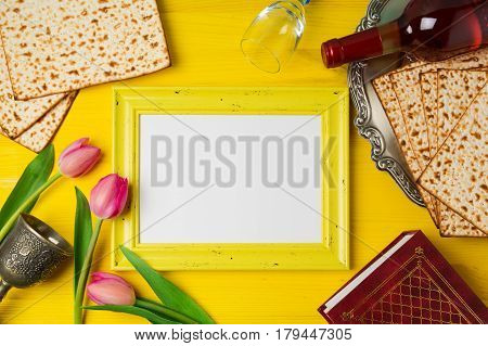 Jewish holiday Passover Pesah celebration with photo frame matzoh and wine bottle on yellow wooden background. View from above