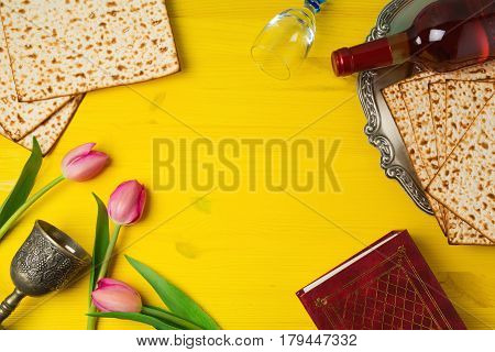 Passover Pesah celebration with matzoh tulip flowers and wine bottle on yellow wooden background. View from above