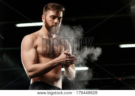 Image of handsome sports man in gym rubbing hands with chalk and looking aside.