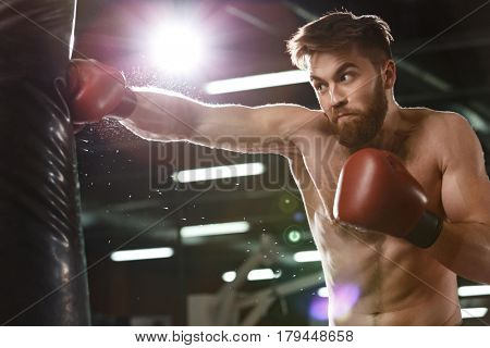 Photo of emotional young strong sports man boxer make exercises in gym and looking aside.