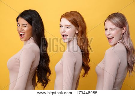Side view image of young winking three ladies standing over yellow background. Looking at camera.