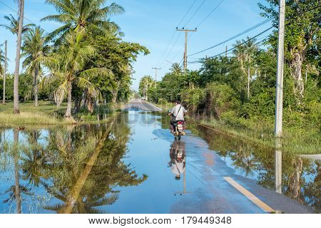 HUA HIN, THAILAND - JANUARY 13, 2017: Motorbiker drives in the countryside south of Hua Hin after heavy rain. The wet season in Thailand was delayed in 2016 with rains continuing into January 2017.