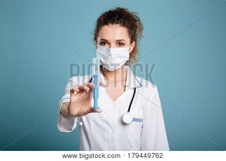 Woman in face surgical mask and white lab coat holding syringe isolated over blue background.