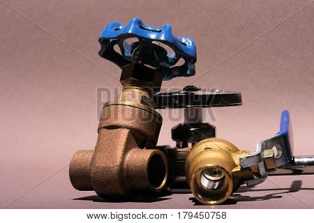 Ball valve and two types of brass shutoffs used in home plumbing.