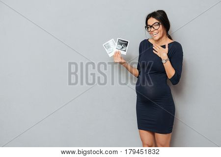 Image of cheerful pregnant business lady standing over grey background. Looking at camera and holding ultrasound scans.
