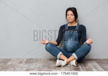 Photo of concentrated pregnant lady sitting on floor over grey background make yoga meditation exercise. Eyes closed.