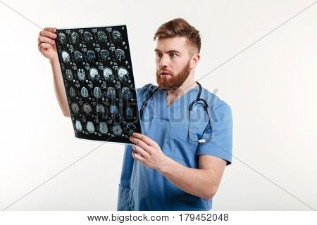 Portrait of a shocked young medical doctor looking at CT scan isolated on white background