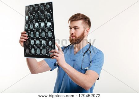 Portrait of a young medical doctor analyzing a CT scan isolated on white background
