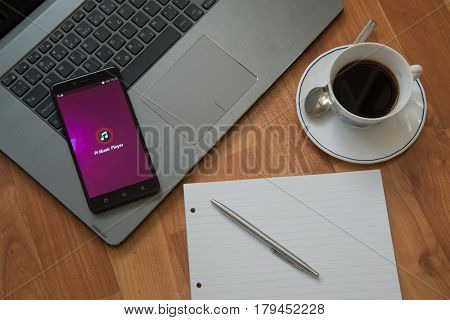 Nitra, Slovakia, march 28, 2017: Pi music player application in a mobile phone screen. Workplace with a laptop, an earphones, notepad, pen and coffee on wooden background