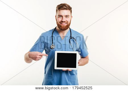 Portrait of a friendly happy medical doctor or nurse pointing finger at blank screen tablet computer isolated on white background