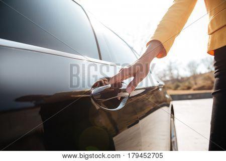Closeup of businesswomen opening the door of black car