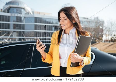 Smiling young businesswoman in yellow jacket with documents in folder using smartphone outdoors