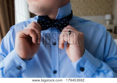 The groom in a blue shirt holding a bow tie in his hands