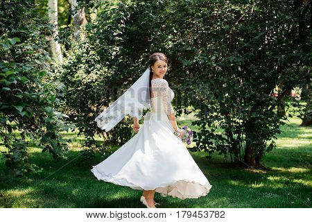 Bride in white dress is spinning in the park. Dress develops in the wind. Happy bride in a wedding dress is spinning
