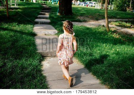 Little girl with pigtails in a colored dress runs on a footpath