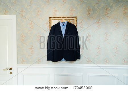 Blue shirt and black jacket on trempel on the wall with a floral pattern near white door. Groom wear