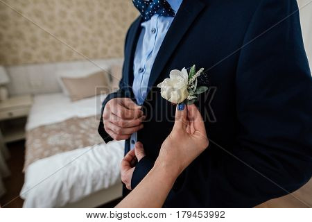 Bride inserting the boutonniere in buttonhole of man in suit