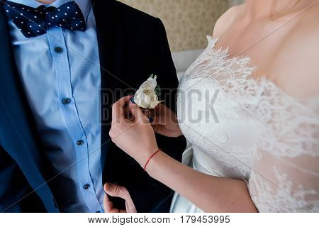 Bride fastens groom boutonniere to buttonhole. Wedding