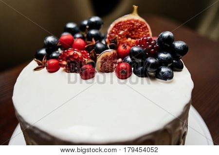 Cake decorated with fresh fruits on the white plate on a wooden table. Wedding cake