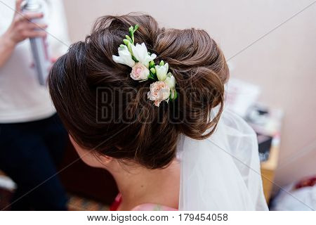 Bride's hairstyle with fresh flowers. Bride's morning
