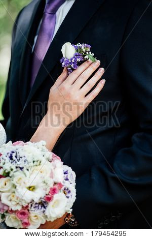Woman inserting the boutonniere in buttonhole of man in suit
