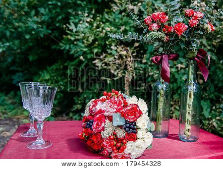 A wedding bouquet of red and white roses and red and blue berries on a burgundy tablecloth next to two glasses and two bottles of flowers. Wedding floral decorations. Flower decorations in transparent glass bottles.