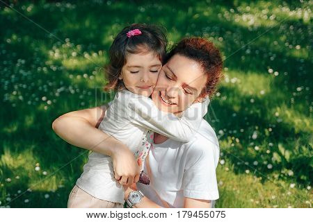 Happy family, mother hugs her daughter. They are happy together.