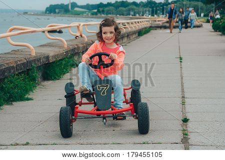 A little girl is riding a pedal kart at the seaside.