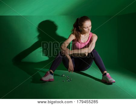Healthy fit body of beautiful young caucasian woman sits on the floor in front of scattered pills