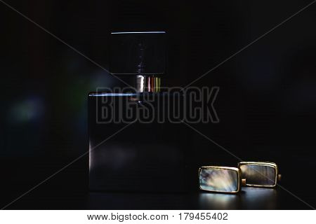 stylish Male perfume with cufflinks over black