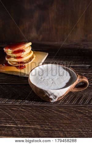 Cappuccino in a ceramic cup cappuccino and fritters сappuccino on a brown background brown ceramic cup with white icing.