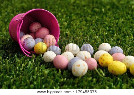 Small speckled easter eggs spilling out of a pink bucket unto artificial grass