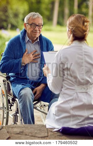 elderly man in wheelchair who don't feel good with nurse outdoor