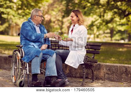 Hospice nurse giving therapy medicine to senior man in wheelchair outdoor
