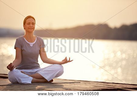 Woman on dock sitting in yoga pose and meditate