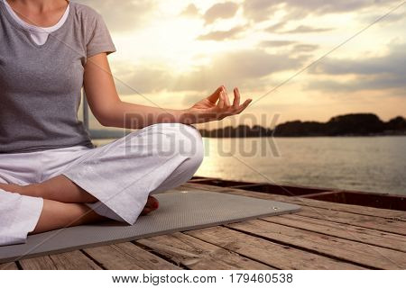 Woman in lotus pose on dock, concept