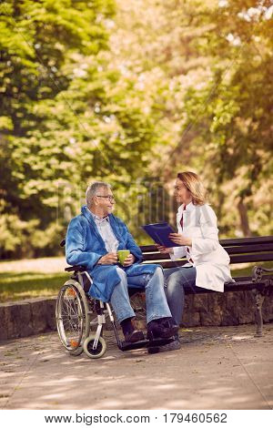 Caring nurse talking with patient in wheelchair checking up the history of the disease outdoor