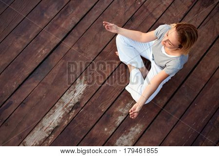 Woman relaxing in yoga pose on dock - top view