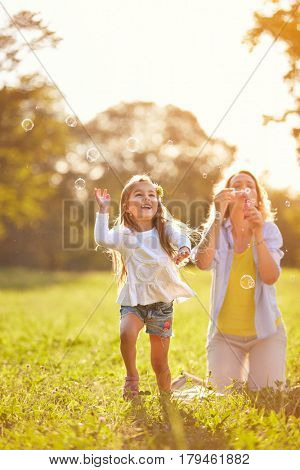 Cheerful girl chase shinny soap bubbles in nature